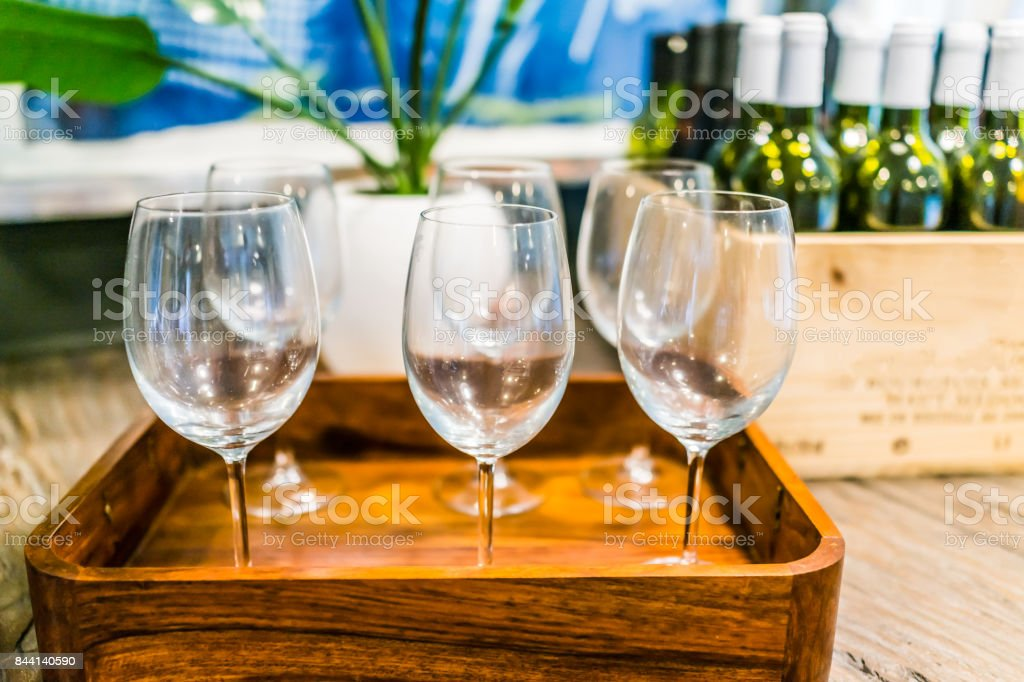 Closeup of empty wine glasses on tray with wooden crate of bottles on table in room stock photo