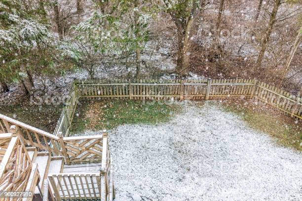 Photo of Closeup of empty wooden deck of house with staircase, steps, stairs, trees, forest, lawn grass in backyard in neighborhood with snow covered ground during blizzard white storm, snowflakes falling in Virginia suburb, single family home