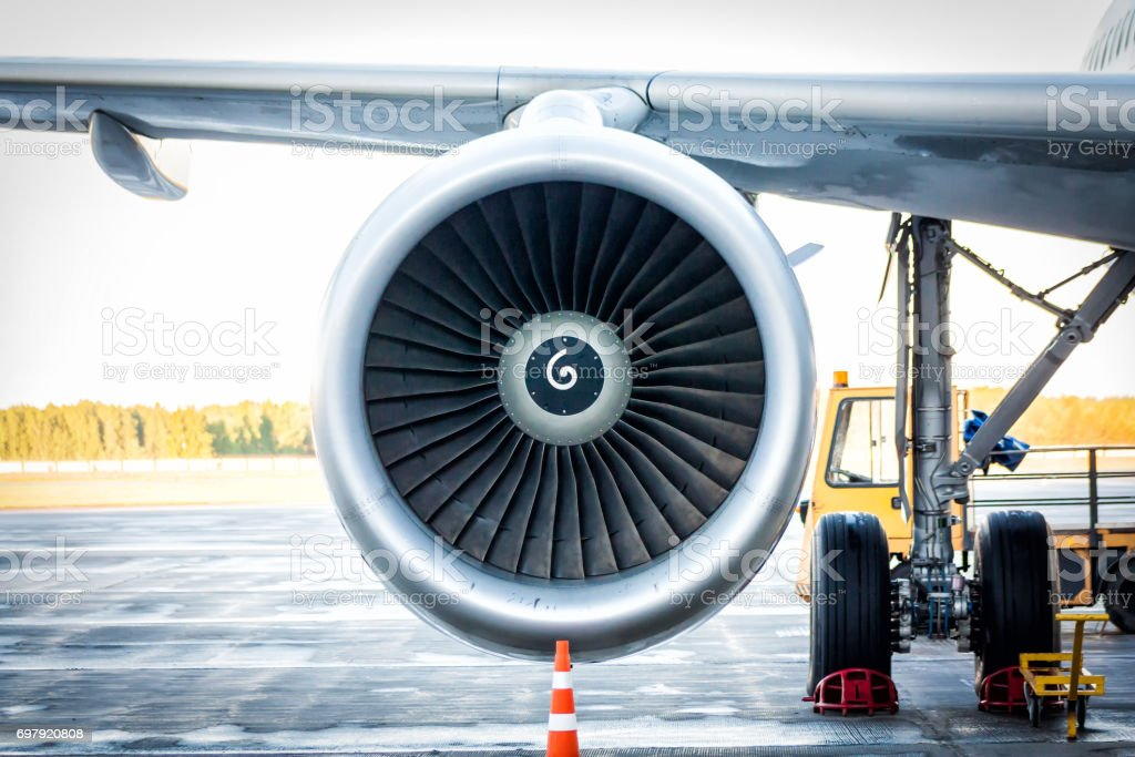 Close-up of engine and main landing gear of passenger airplane стоковое фото