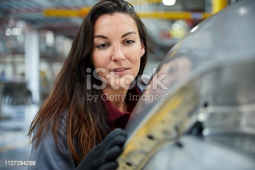 istock Close-up of engineer examining car in industry 1127294259