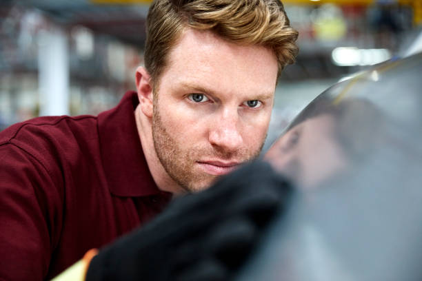 Close-up of engineer touching car part in industry stock photo