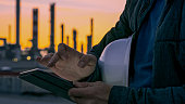 Close-up shot of the hands an engineer with a white hardhat using a tablet with an oil refinery visible in the background during sunset.