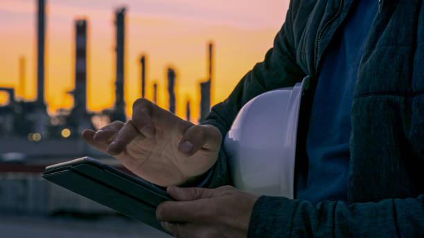 Close-up of engineer using tablet near oil refinery. Close-up shot of the hands an engineer with a white hardhat using a tablet with an oil refinery visible in the background during sunset. chemical plant stock pictures, royalty-free photos & images