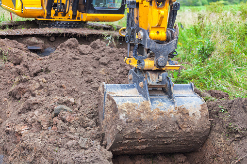 Yellow excavator on the gas pipeline performs excavation work