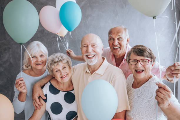 Close-up of excited pensioners Close-up of happy, excited pensioners during a birthday party, holding colorful balloons. Active seniors concept. retirement community stock pictures, royalty-free photos & images