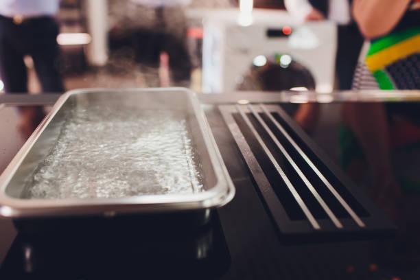 nahaufnahme von auspuffhaube und keramikkochplatte in der neuen modernen küche. - backofenfenster reinigen stock-fotos und bilder