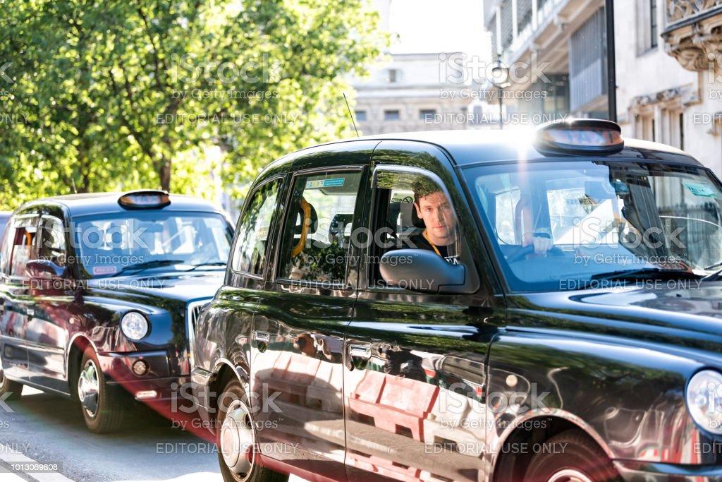 Closeup de táxi preto caro e motorista na rua road, jovem volante esperando no trânsito - foto de acervo
