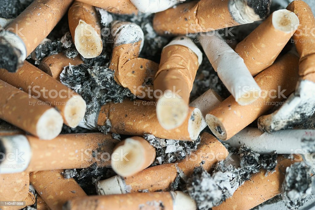 Close-up of extinguished cigarette butts stock photo