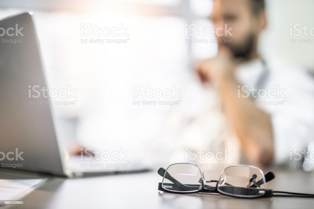 Close-up of eyeglasses on busy doctor's desk. stock photo