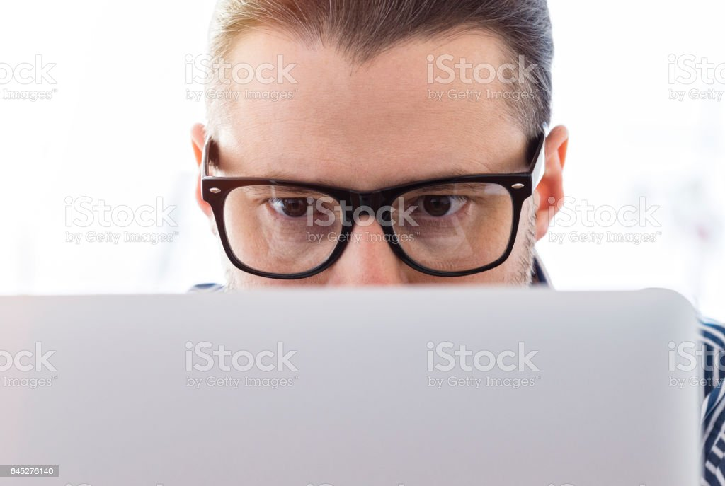 Close-up of eyes, man working on a laptop stock photo