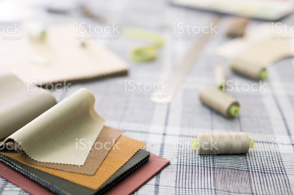Close-up of fabric patterns and thread spools on tailors table in workshop stock photo