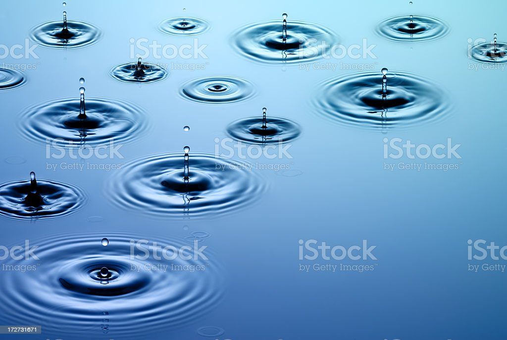 Close-up of falling raindrops and associated ripples stock photo