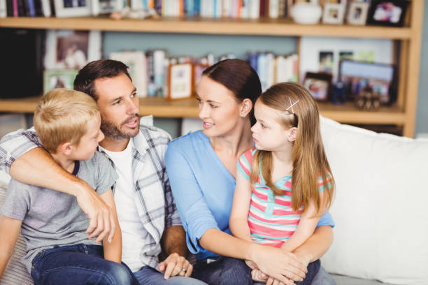 Close-up of family discussing on sofa stock photo