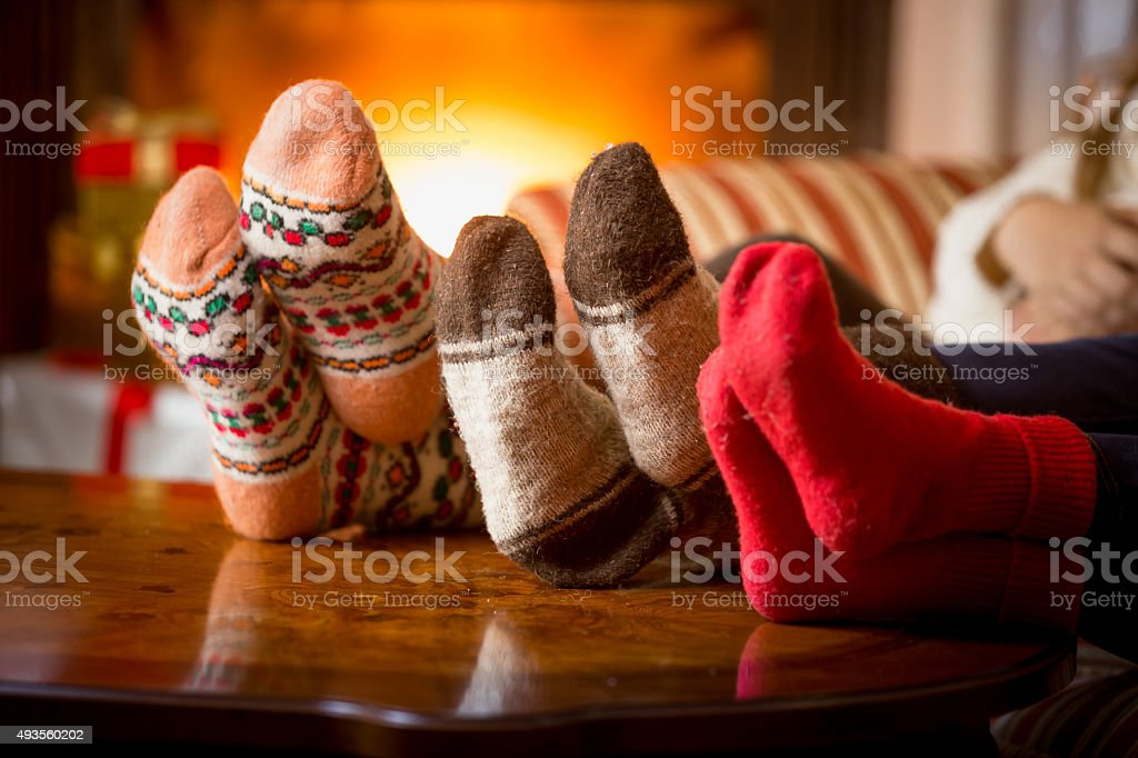 Closeup of family feet in wool socks at fireplace stok fotoğrafı