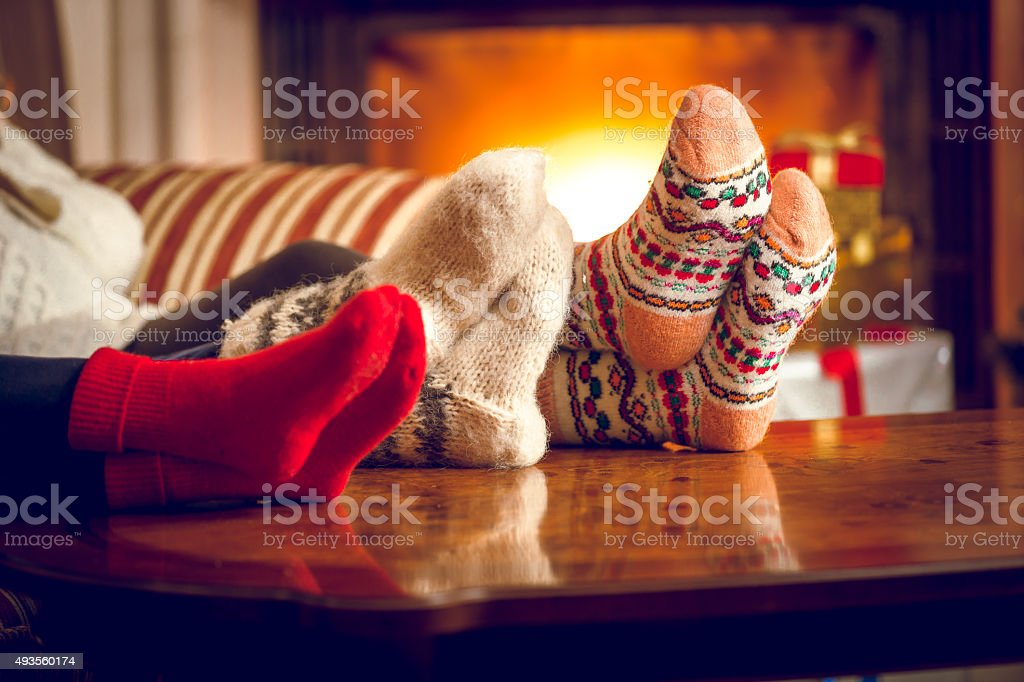 Closeup of family warming feet at fireplace stock photo