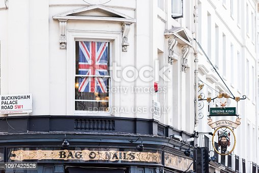istock Closeup of famous Bag O'Nails of Nails pub bar sign on Buckingham Palace Road with Greene King entrance and nobody 1097422528
