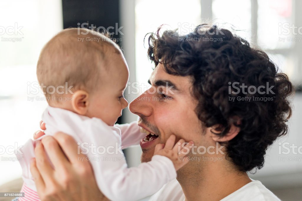 Close-up of father kissing happy son stock photo