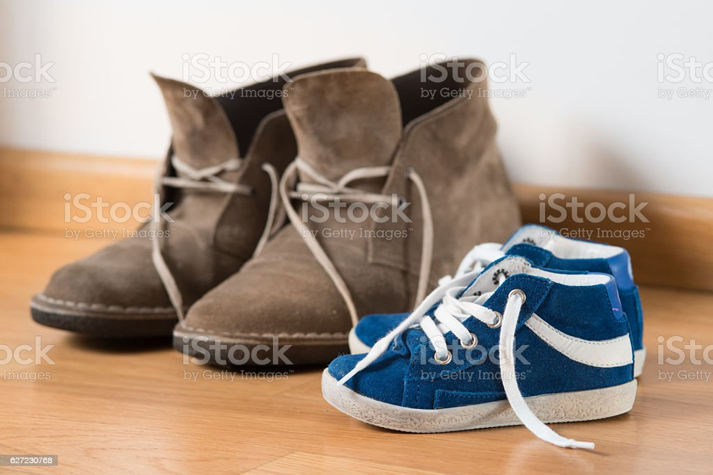 Closeup of father's shoes close to child's shoes stock photo