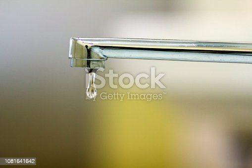 Close-up of faucet with turned drop water in modern bathroom. Horizontal crop with shallow depth of field
