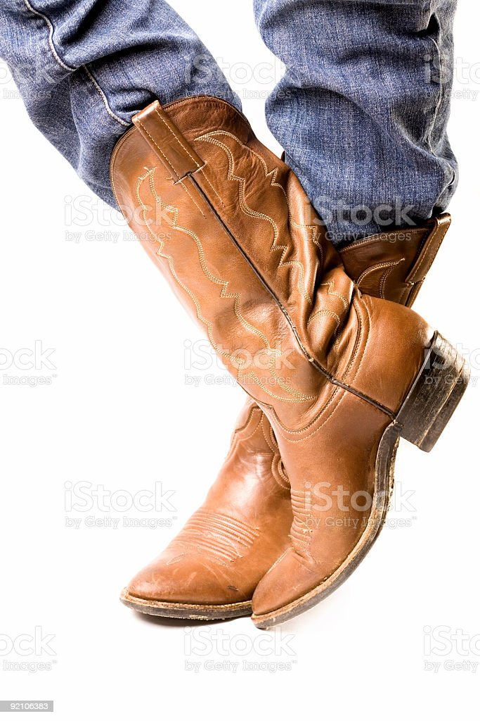 Close-up of feet in cowboy boots and jeans royalty-free stock photo