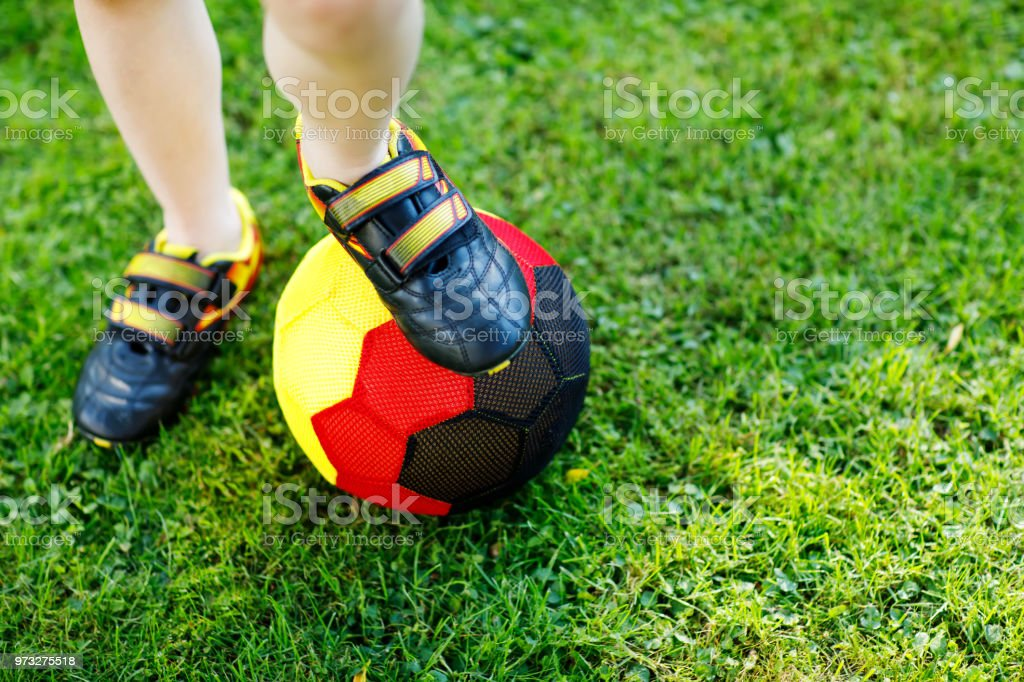 87f202cc859 Close-up of feet of kid boy with football and soccer shoes in German  national colors - black