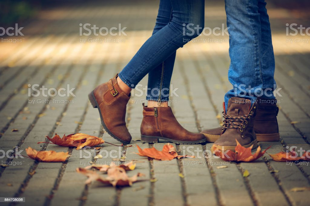 Close-up of feet of romantic couple in autumn park. stock photo