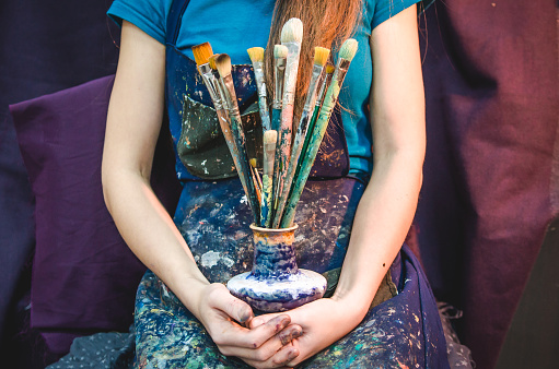 istock Closeup of female artist hands with paintbrushes 898696250