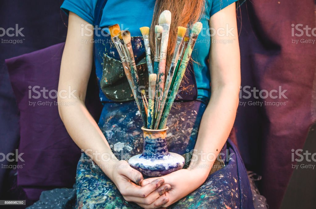 Closeup of female artist hands with paintbrushes stock photo