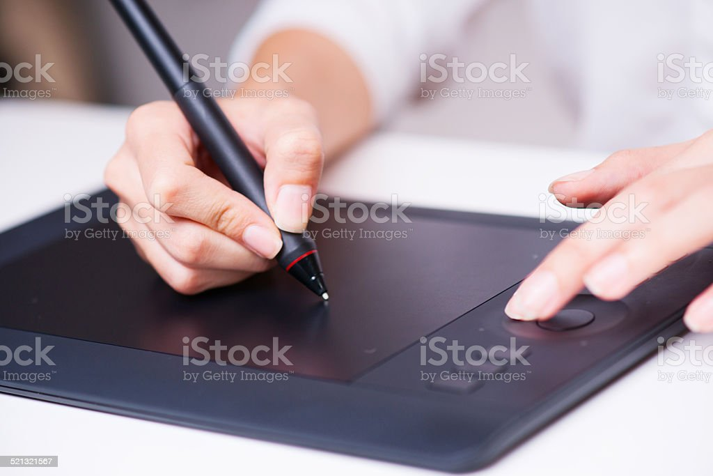 closeup of female dressmaker sketching and drawing with graphic tablet. stock photo