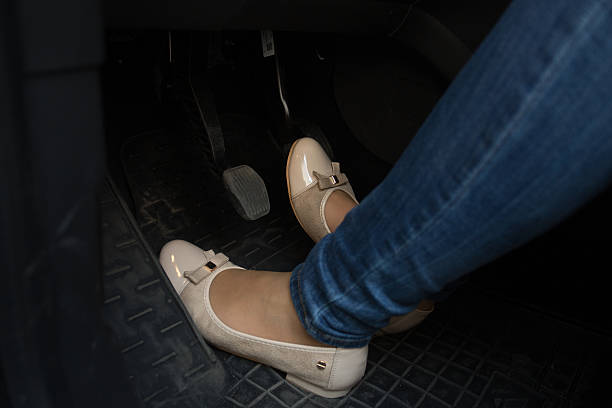 Closeup of female driver feet on car pedals Closeup photo of female driver feet on car pedals vehicle clutch stock pictures, royalty-free photos & images