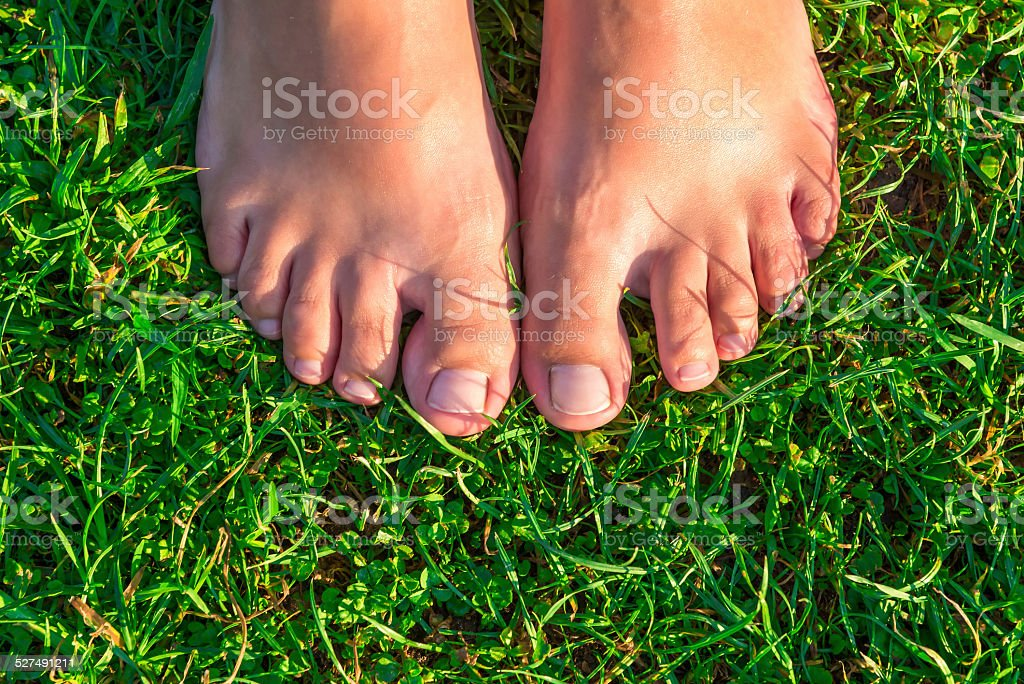close-up of female feet on grass stock photo