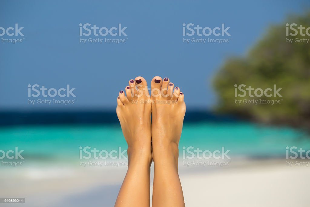 Close-up of female foot in the blue water stock photo