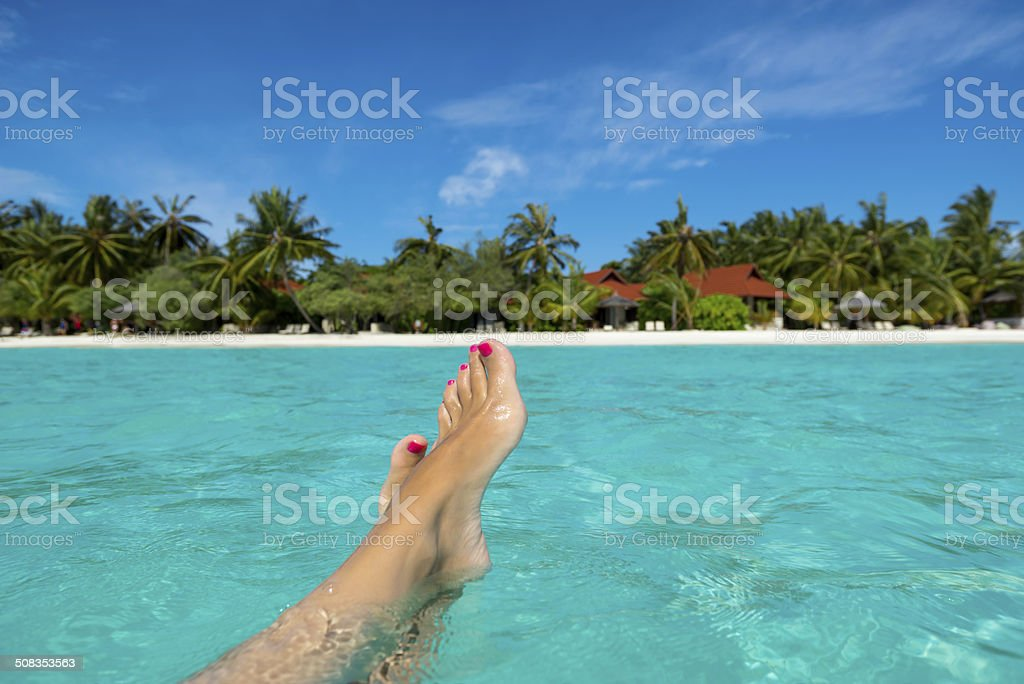 Close-up of female foot on the tropical beach. stock photo