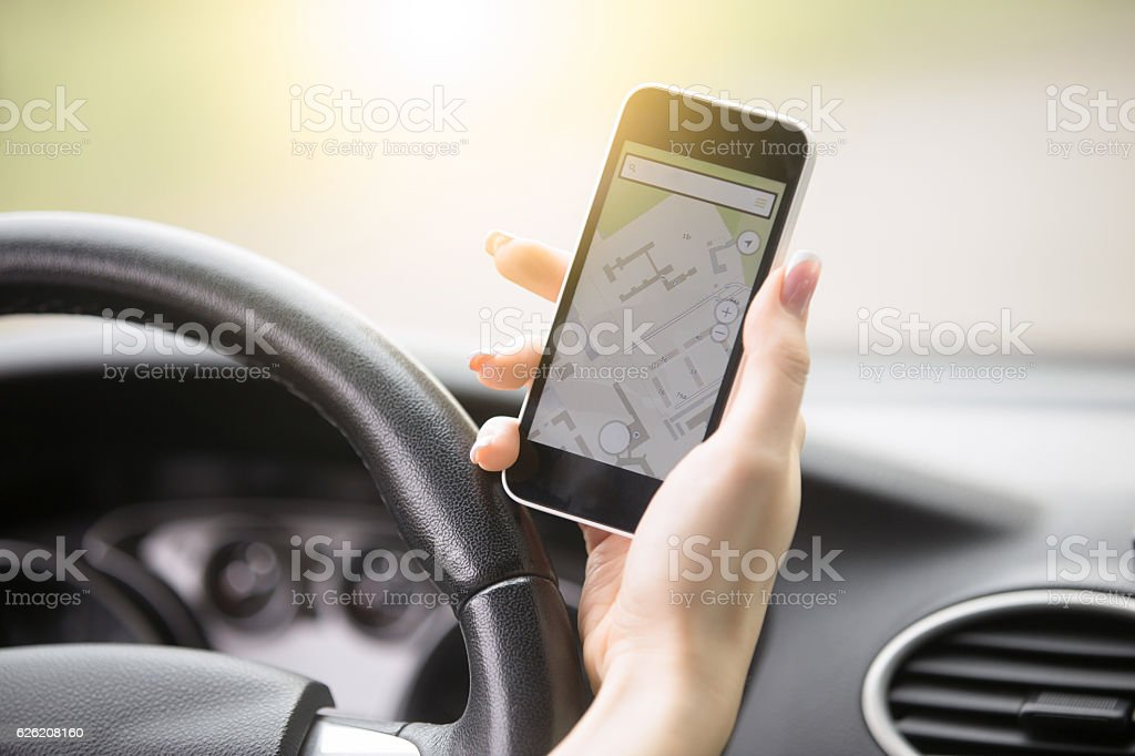 Close-up of female hand holding her phone with navigation stock photo