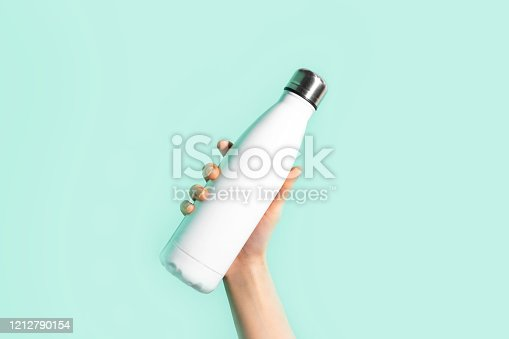1129148925 istock photo Close-up of female hand, holding white reusable steel stainless eco thermo water bottle with mockup, isolated on background of cyan, aqua menthe color. Be plastic free. Zero waste. 1212790154