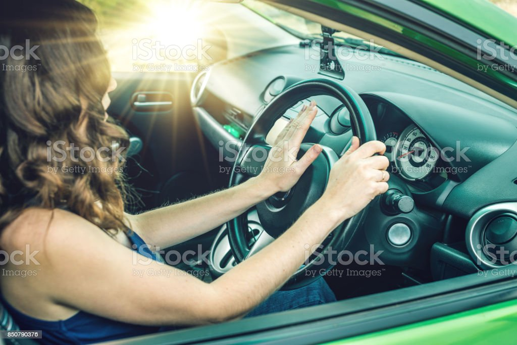 Closeup of female hand on the steering wheel presses the horn button in the car. Concept irritation while driving stock photo