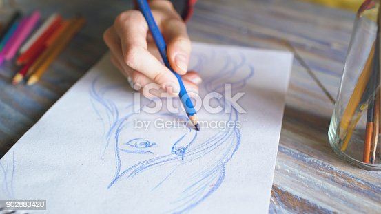 istock Closeup of female hand painting sketch on paper notebook with pencils. Woman artist at work 902883420