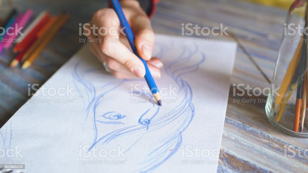 Closeup of female hand painting sketch on paper notebook with pencils. Woman artist at work stock photo