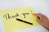 Close-up of female hand pointing at paper with Thank You text