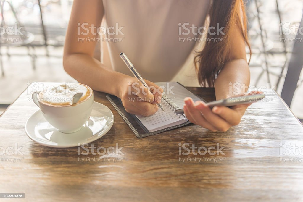 Close-up of female hand writing note beside cup of cappuccino stock photo