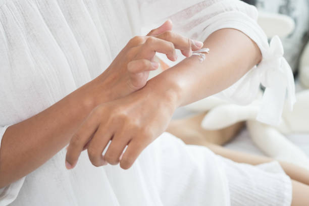 Closeup of female hands applying cream on her arm. Make up, healthy skin, beauty shot, cute asian woman concept stock photo