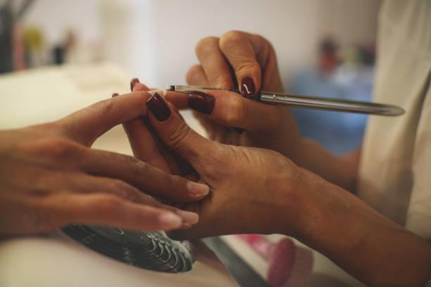 nahaufnahme der weiblichen hände manikürt werden in einem schönheitssalon. - nailstudio stock-fotos und bilder