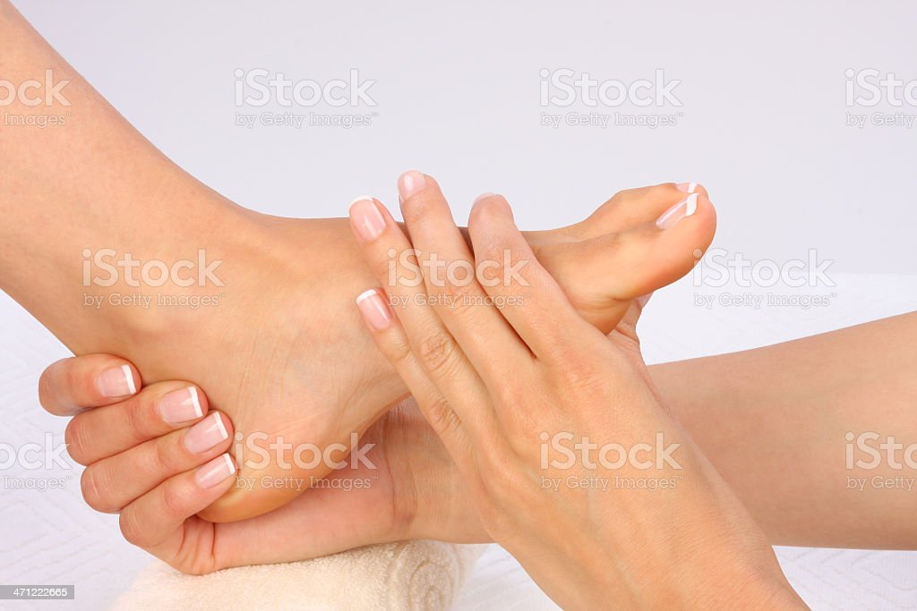 Close-up of female hands giving a foot massage near a towel stock photo