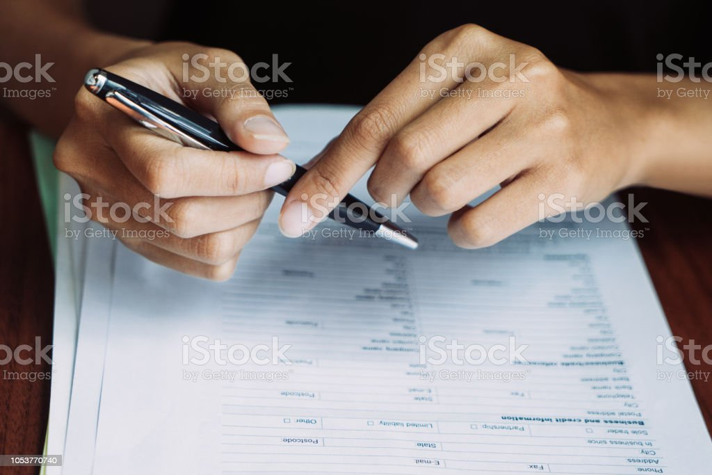 Close-up of female hands holding pen over application form going to...