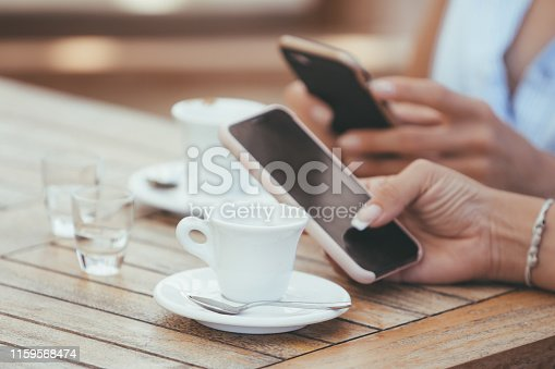 911294484istockphoto Close-up of female hands holding phones chatting on social network or shopping online in cafe with two cups of italian espresso coffee. Compulsive smartphone and internet use (addiction) concept 1159568474
