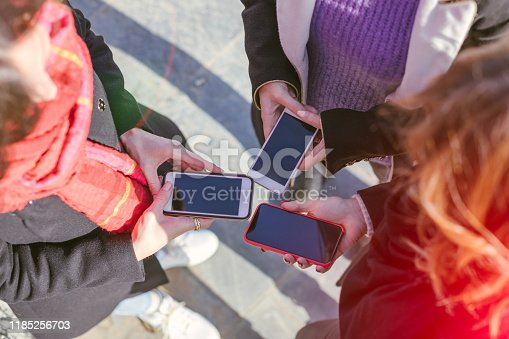 911294484istockphoto Close-up of female hands holding smartphones, top view - phone and social media addiction concept 1185256703