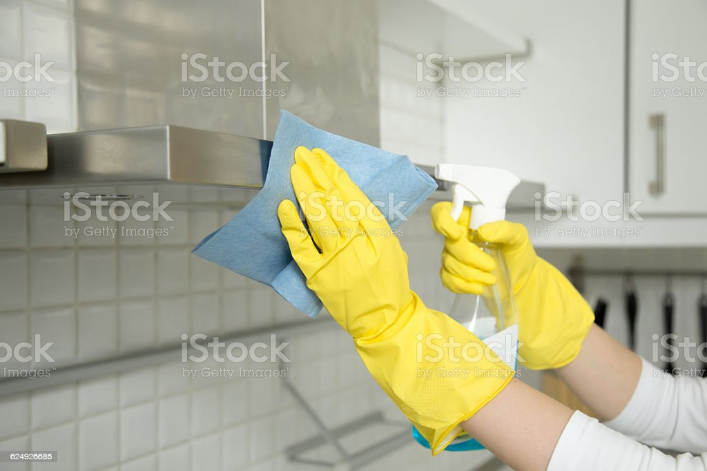 Closeup of female hands in gloves cleaning the extractor hood stock photo