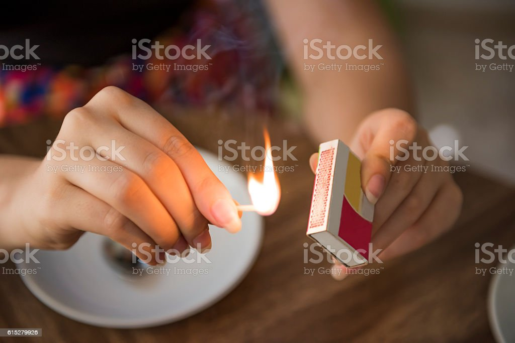 Closeup of female hands lighting a match on box - Royalty-free Adult Stock Photo