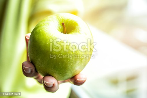 Close-up of female hands showing or giving apple