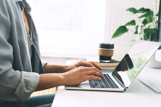 Closeup of female hands typing text on laptop keyboard. Woman working or studying at home office with cup of coffee. Freelancer working place. stock photo